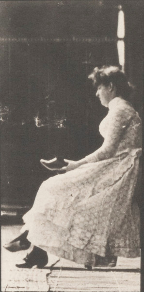 Woman in long dress putting on shoes and rising from a chair