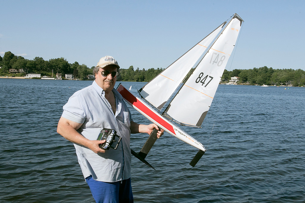. Having some fun radio controlled sailing boats on Lake Whalom in Lunenburg Thursday, August 1, 2019 was Leominster residents Russ Hume and Sam Giadone. The boats they were sailing were called Dragon sailing boats. Hume got into the hobby about 8 months ago and Giadone, hat, has been into it for about three months. Giadone shows off what the boat looks like out of the water. SENTINEL & ENTERPRISE/JOHN LOVE