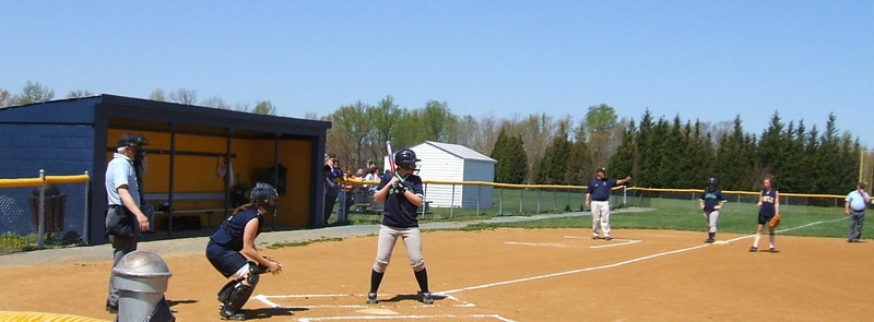 Ashley Kemp at the plate, Coach Reggie Brann, and Jessica Shearwood at third base.