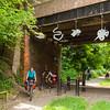 Под мостом висят  развеселые контурные персонажи из листового металла