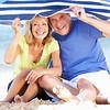 Senior Couple Sheltering From Sun Under Beach Umbrella