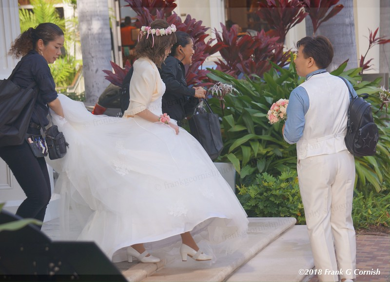 A bride steps to her waiting limo while her groom holds her bouquet and attendees hold her train on the sidewalks of Honolulu, Hi