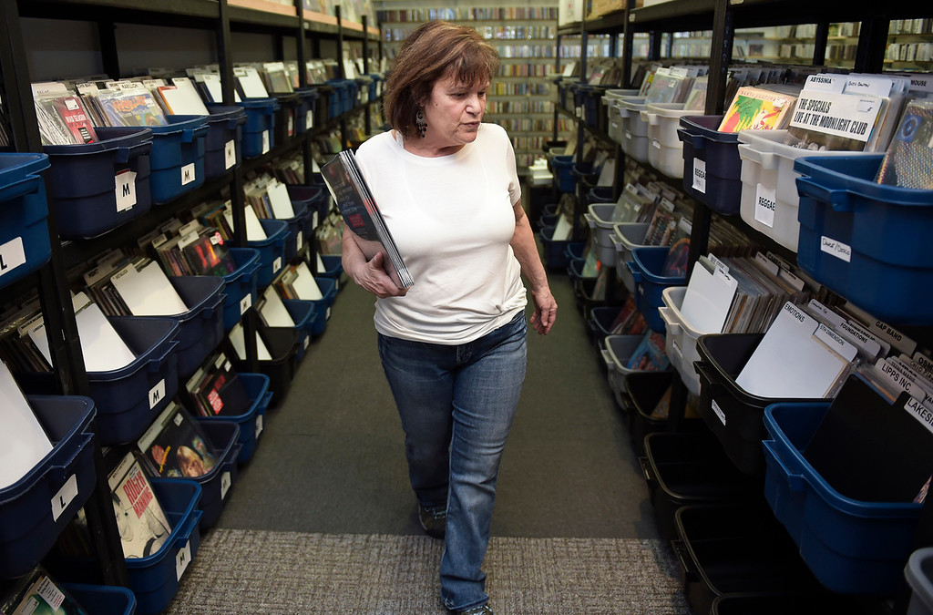 . Owner Gale Taylor stocks LPs at Recycled Records, 1067 S. Hover St., Tuesday afternoon. Lewis Geyer/Staff Photographer April 10, 2018