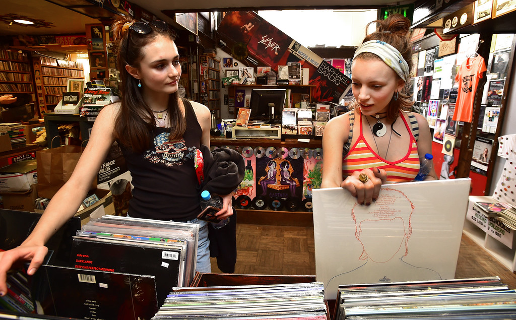 . Lindsay Gildersleeve, left and Olivia Colender talk as they look over vinyl records in Albums on the Hill on 13th Street on University Hill in Boulder on Tuesday.  Paul Aiken Staff Photographer April 10, 2018