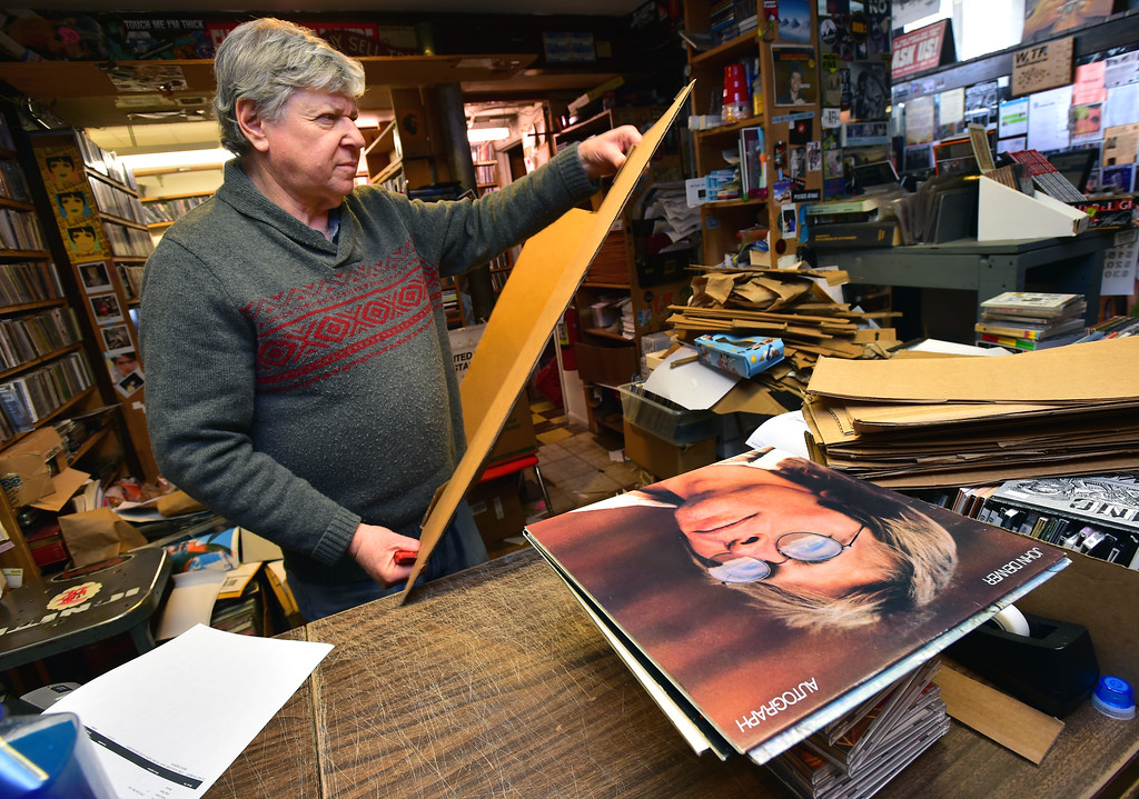 . Andy Schneidkraut, owner of Albums on the Hill, works behind the counter in his store on 13th Street on University Hill in Boulder on Tuesday.  Paul Aiken Staff Photographer April 10, 2018