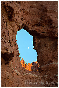 Moon rising in a red rock window, near Fisher Towers
