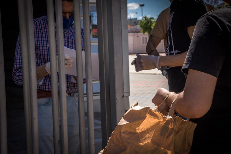 """Reparto de alimentos en Fundación don Bosco: Una familia se identifica en la puerta. La Fundación Alalá ha comprobado que la escasez de comida se ha agravado en particular en las familias que dependen sobre todo de la venta ambulante: """"Familias que vivían medianamente ordenadas y se están quedando ahora sin ningún recurso"""" afirma la Directora de la Fundación Alalá Blanca María Parejo."""