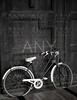 Aged vintage black bicycle, big wooden door, black and white