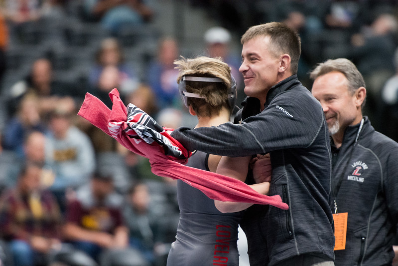 Loveland coach Troy Lussenhop hugs Cody Thompson after winning his fifth-place match during the 4A state wrestling tournament Saturday Feb. 17, 2018 at the Pepsi Center in Denver. (Cris Tiller / Loveland Reporter-Herald)