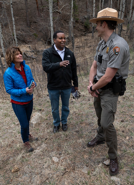 Neguse, center, shares a laugh with Rocky Mountain National Park Superintendent Darla Sidles and a park ranger.