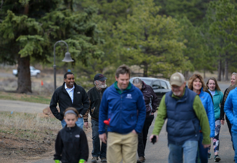 Colorado Congressman Joe Neguse, left, walks with his constituents to a plot of land near the Beaver Meadows Visitor Center to help seed and mulch it as part of a restorative effort on April 20. Following the volunteer work, Neguse fielded questions during a Community Service Town Hall outside the visitor center.
