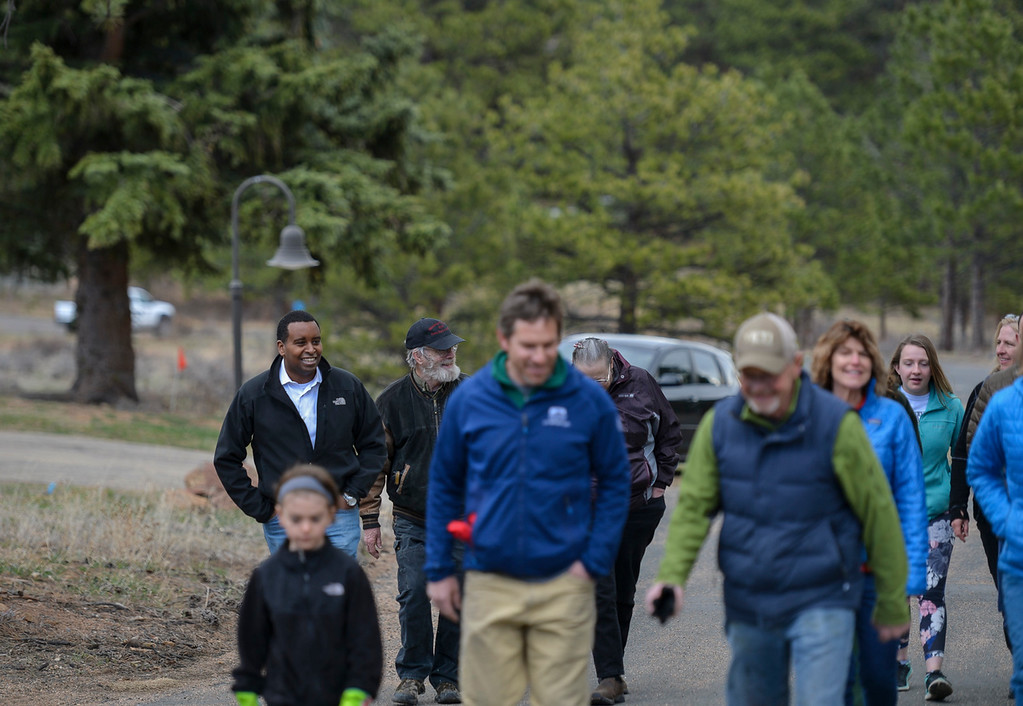 . Colorado Congressman Joe Neguse, left, walks with his constituents to a plot of land near the Beaver Meadows Visitor Center to help seed and mulch it as part of a restorative effort on April 20. Following the volunteer work, Neguse fielded questions during a Community Service Town Hall outside the visitor center.