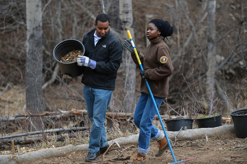 Joe Neguse, left, chats with a Rocky Mountain National Park volunteer during an Earth Day seeding and mulching restoration effort in the park on April 20.