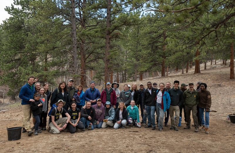 Neguse and the group of volunteers who helped seed and mulch some land in Rocky Mountain National Park pose for a photo.