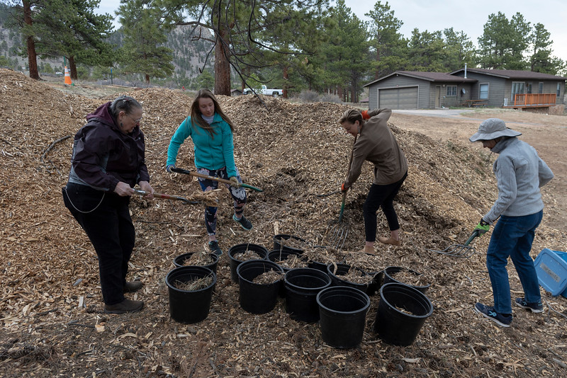 Several volunteers worked hard refilling buckets with mulch.