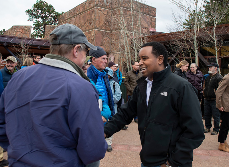 Colorado Congressman Joe Neguse, left, shakes hands with his constituents in the second congressional district of Colorado at the Beaver Meadows Visitor Center on April 20.