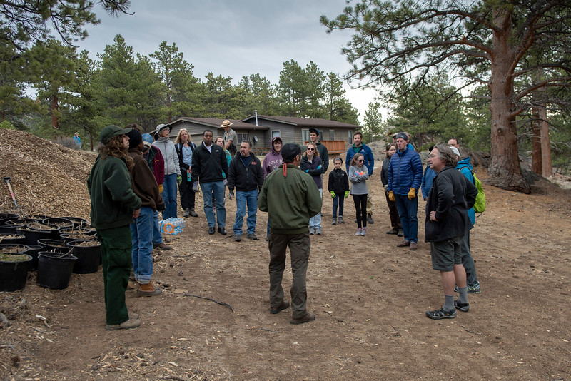 A Rocky Mountain National Park official explains to Neguse and a group of volunteers how they will seed and mulch an area of land near the Beaver Meadows Visitor Center on April 20.