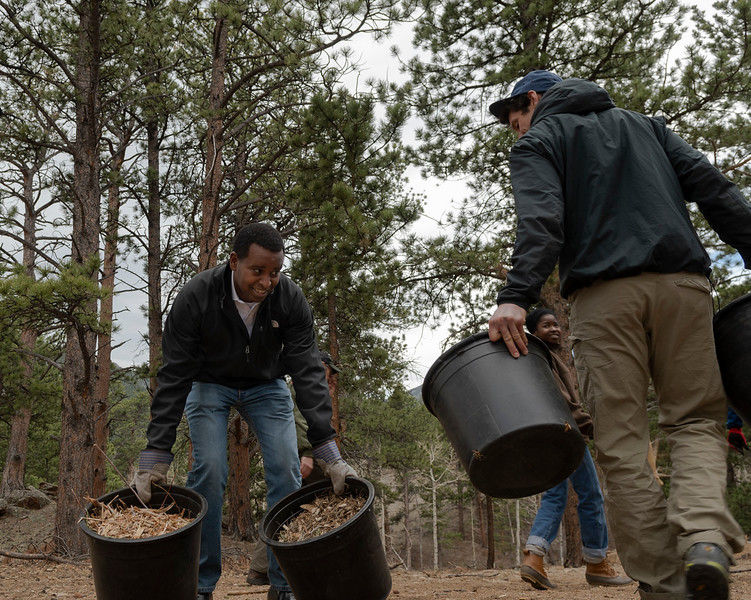 Joe Neguse, left, picks up two buckets of mulch on April 20. The freshman Congressman got his hands dirty before addressing policy with his constituents during a Community Service Town Hall following the Earth Day land restoration event.