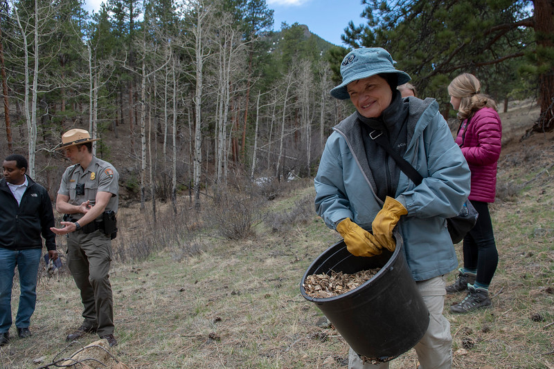 A resident from the second congressional district of Colorado smiles as she helps restore some land in Rocky Mountain National Park as part of an Earth Day effort.
