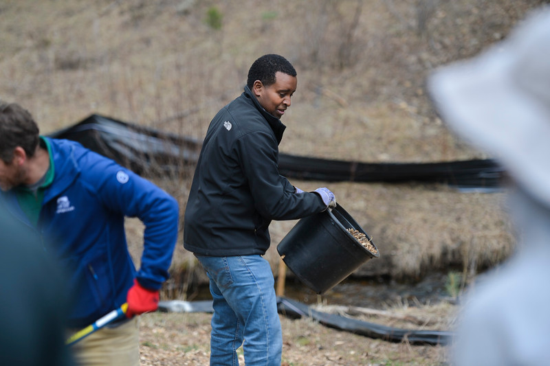 Colorado Congressman Joe Neguse prepares to dump out a bucket of mulch in Rocky Mountain National Park as part of a land restoration effort for Earth Day.