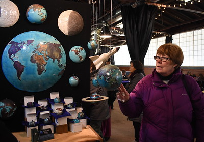 Donna DeLuca , Royal Oak, examines artist Stan Baker's ceramic world globes.  Visitors browse the jewelry, ceramics, glass, painting, sculpture and other works of 60 juried artists at the 2nd annual Spring Art Fair at the Farmers Market in Royal Oak, Michigan on April 5, 2018. Hosted by The Guild of Artists and Artisans, the event, which runs Friday April 6 from noon to 10pm, kicks off the Art Fair season and includes music, food trucks and craft beverages. Officials expect roughly 7,000 people to attend the 2-day event.  (Photo by Brandy Baker)