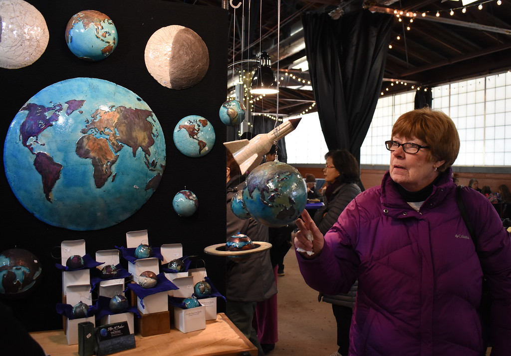 . Donna DeLuca , Royal Oak, examines artist Stan Baker\'s ceramic world globes.  Visitors browse the jewelry, ceramics, glass, painting, sculpture and other works of 60 juried artists at the 2nd annual Spring Art Fair at the Farmers Market in Royal Oak, Michigan on April 5, 2018. Hosted by The Guild of Artists and Artisans, the event, which runs Friday April 6 from noon to 10pm, kicks off the Art Fair season and includes music, food trucks and craft beverages. Officials expect roughly 7,000 people to attend the 2-day event.  (Photo by Brandy Baker)