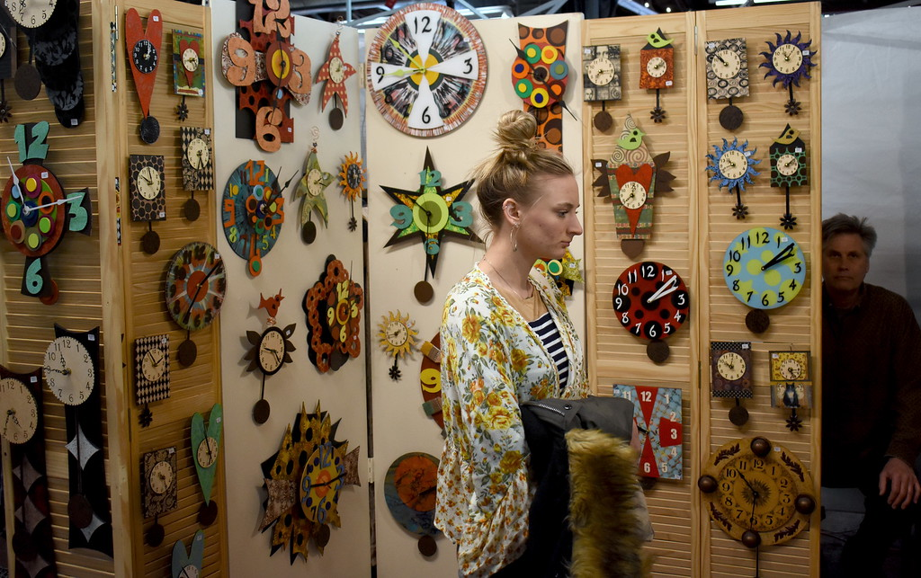 . Stephanie Hill, Royal Oak, checks out the wood clocks made by artist Duane Scherer, Lathrup Village.   Visitors browse the jewelry, ceramics, glass, painting, sculpture and other works of 60 juried artists at the 2nd annual Spring Art Fair at the Farmers Market in Royal Oak, Michigan on April 5, 2018. Hosted by The Guild of Artists and Artisans, the event, which runs Friday April 6 from noon to 10pm, kicks off the Art Fair season and includes music, food trucks and craft beverages. Officials expect roughly 7,000 people to attend the 2-day event.  (Photo by Brandy Baker)