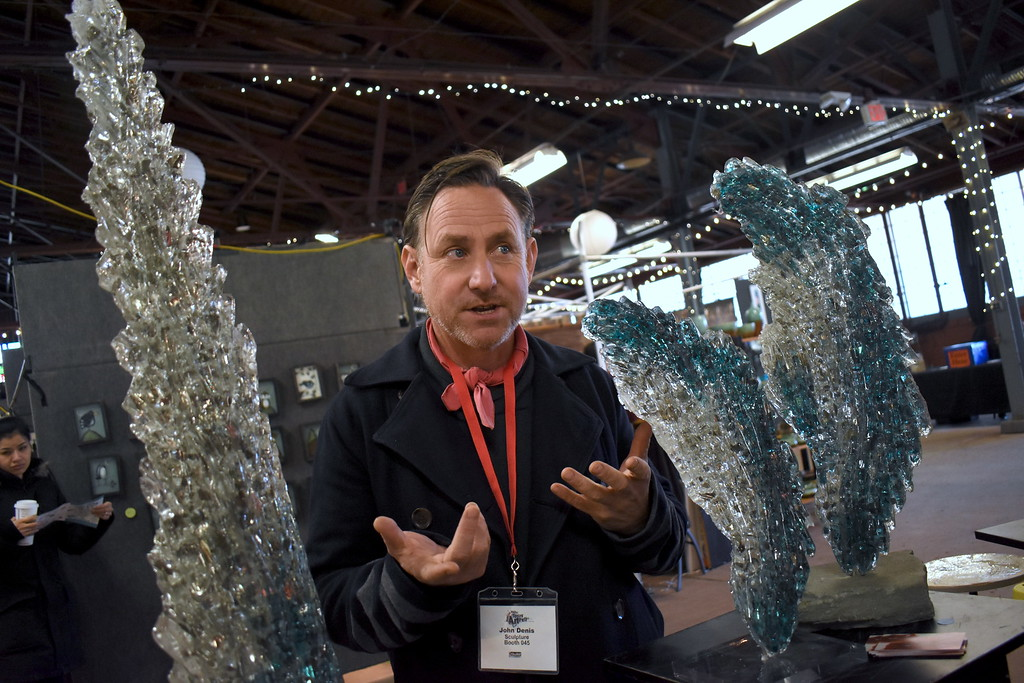 . John Denis talks about his water form sculptures made of recycled glass and acrylic. He is from Chicago.  Visitors browse the jewelry, ceramics, glass, painting, sculpture and other works of 60 juried artists at the 2nd annual Spring Art Fair at the Farmers Market in Royal Oak, Michigan on April 5, 2018. Hosted by The Guild of Artists and Artisans, the event, which runs Friday April 6 from noon to 10pm, kicks off the Art Fair season and includes music, food trucks and craft beverages. Officials expect roughly 7,000 people to attend the 2-day event.  (Photo by Brandy Baker)
