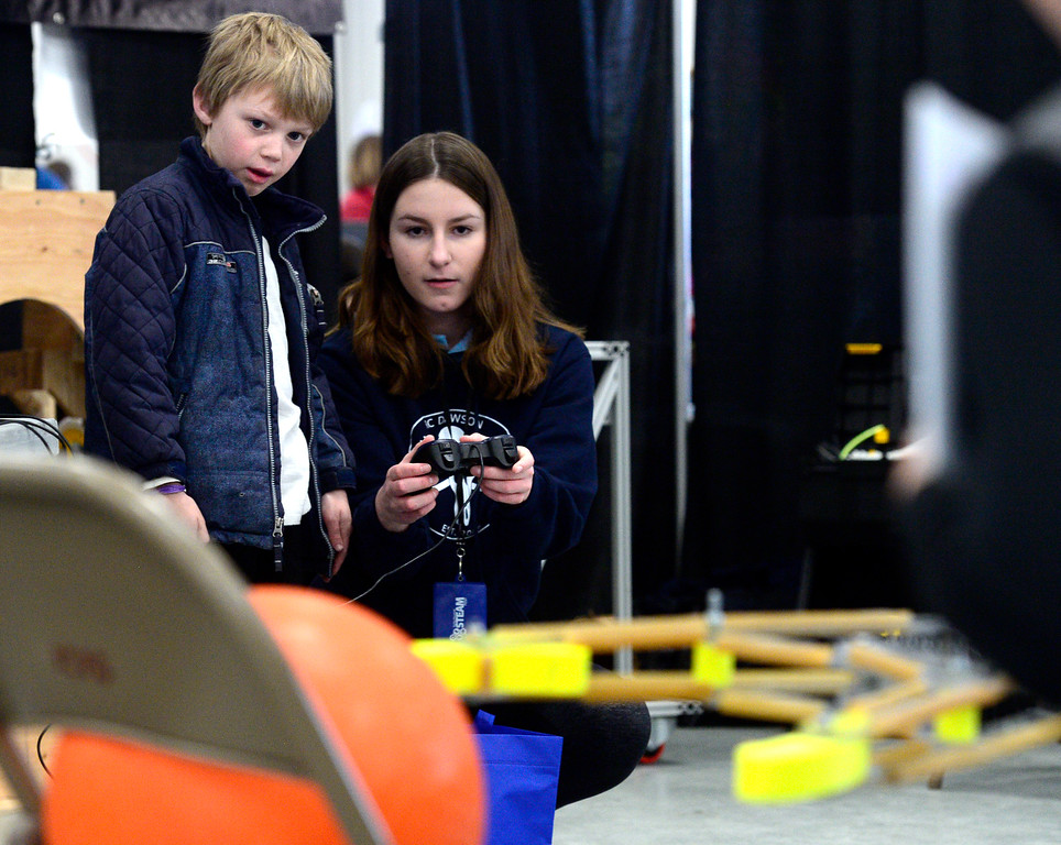 . LONGMONT, CO - MARCH 3, 2019 Amanda Stevens of the RC Dawson school robotics club shows Jake Martin, 9, how to position a robot arm to pick up a ball at Rocky Mountain STEAM Fest 2019 at the Boulder County Fairgrounds in Longmont on March 3, 2019.  For more photos go to timescall.com. Paul Aiken / For the Camera
