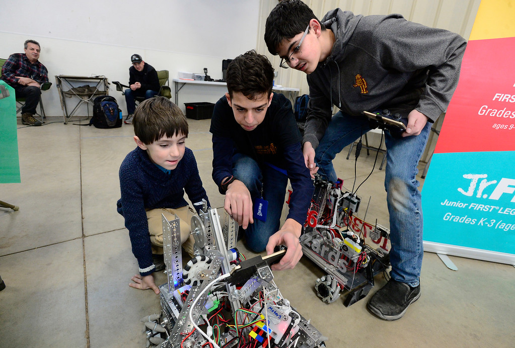 . LONGMONT, CO - MARCH 3, 2019 Liam Buchanan, 7, at left, gets some tips on how to run a robot from Dominic Spina, and Austin Martinez, right, in the First Tech Challenge robotics booth at Rocky Mountain STEAM Fest 2019 at the Boulder County Fairgrounds in Longmont on March 3, 2019.  For more photos go to timescall.com. Paul Aiken / For the Camera