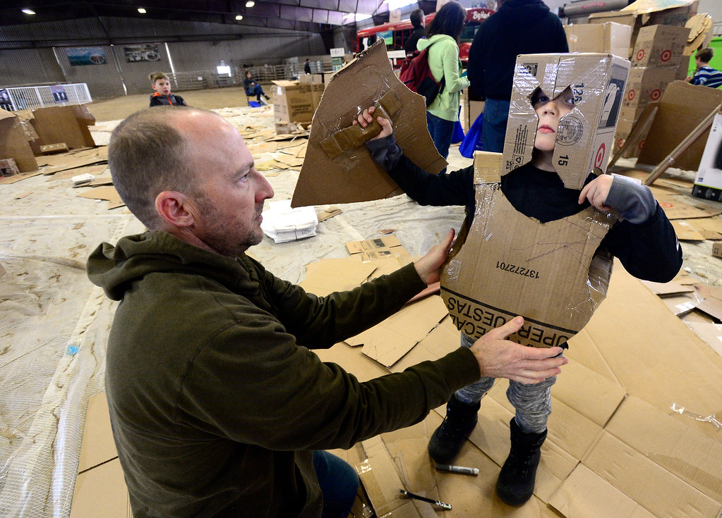 . LONGMONT, CO - MARCH 3, 2019 Cory Bowd helps his son Beckham, 5, try on his cardboard armor they made together at Rocky Mountain STEAM Fest 2019 at the Boulder County Fairgrounds in Longmont on March 3, 2019.  For more photos go to timescall.com. Paul Aiken / For the Camera