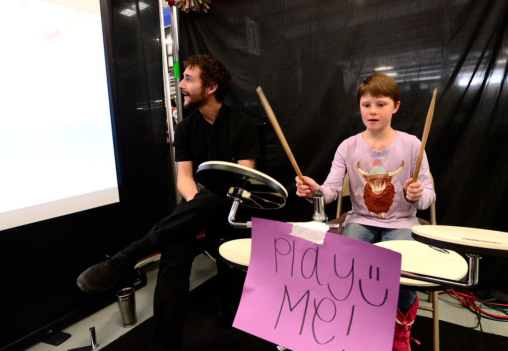 . LONGMONT, CO - MARCH 3, 2019 Carmen Rollins, 9, tries out an electric drum kit as Jack MCahan from the University of Colorado Experience Design program listens in at Rocky Mountain STEAM Fest 2019 at the Boulder County Fairgrounds in Longmont on March 3, 2019.  For more photos go to timescall.com. Paul Aiken / For the Camera