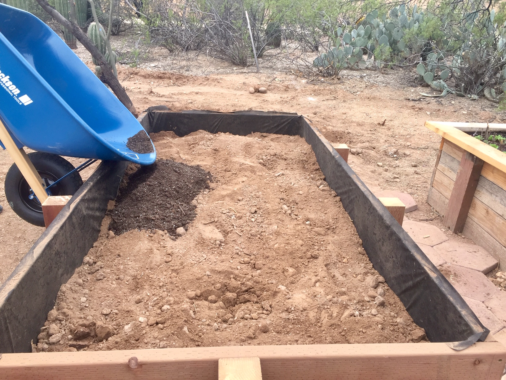 filling raised garden bed with organic soil