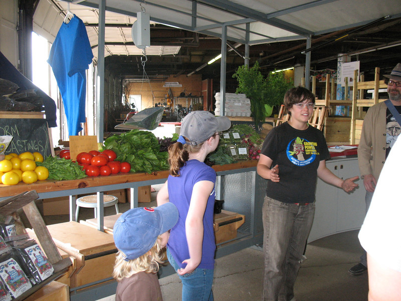 Erica Hougland, urban farmer and tour guide for Growing Power, starts our trip at the farmstand by the Iron Street entrance.