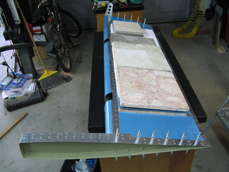 The bottom skin gets weighed down with some heavy tiles. This pushes the skin down on to the spar. The bottom skin is attached to the spar with a combination of pull rivets and regular rivets, depending on how your particular squeezer yokes can fit through the openings for the eyebolts. I was able to go about 2.5 inches on either side of the cut outs with regular rivets.