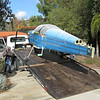 I had borrowed a flat bed trailer to move the fuselage, since it was just a bit too tall to fit in my enclosed trailer. The flat bed was 7 feet wide, and the width between the main gear is 7 feet 5 inches. There was no way I was going to get the gear to sit between the side rails on the trailer. I opted instead to just call a flat bed tow truck. For $100 it was the way to go. We pushed it up in place, then winched all of the wheels down securely.