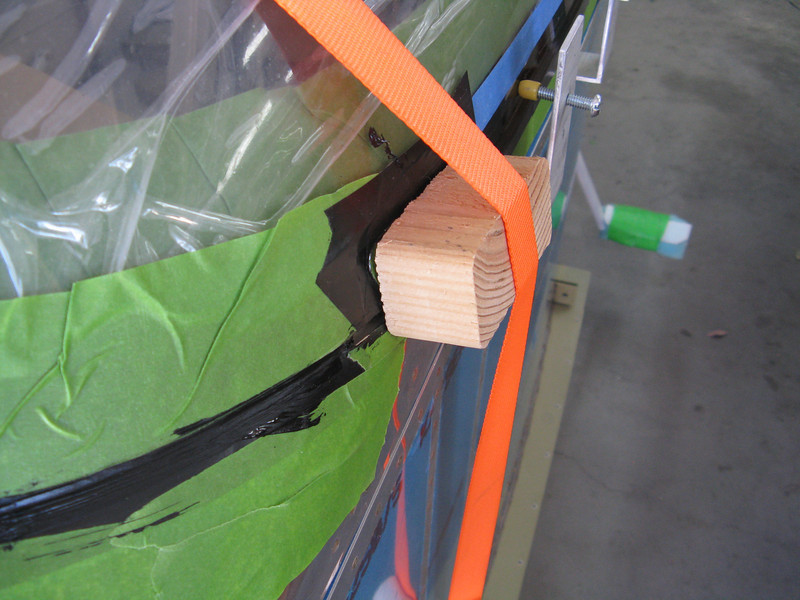 """Some wood blocks are pushed up against the """"ears"""" on the canopy frame and held in place with a tie down strap."""