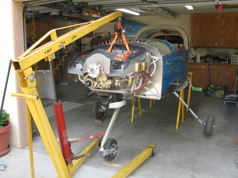 I moved the airplane into the center of the garage and lifted it up with the engine hoist. Straps go to the engine mount, not the engine. A saw horse was put under the rear wing spar carry through, and then the fuselage was lowered until it was leveled.