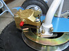 This picture gives a view of how the brake caliper floats on the pins and clamps on to the brake disc. The 2 bolts on the left side of the caliper come out to split the 2 disc brake pads so that you can get one on the interior (outboard side) of the disc and the piston section on the inboard side.