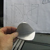A large chunk of Aluminum angle is cut and shaped to create this tank attach angle. Cutting and grinding this gets it pretty hot, so it took hours to finally bring it down to the proper shape. I made a copy of the plans, then cut out templates on paper to transfer the curving shape on to the aluminum with a sharpie pen. This is the right tank angle, and it still needs to be drilled for rivets.