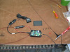 I passed my Technician Class radio license and am now KJ6YRP, according to the FCC. This opens the door to using APRS tracking. I bought this APRS tracker from Byonics. It runs off 12V from a car power adapter, has a self contained GPS puck, and comes with a magnetic whip antenna. I took the top off the APRS unit to get a peek inside.
