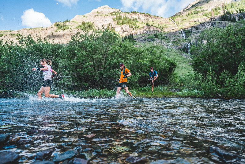 Caroline Chaverot leads Joe Grant into the creek at Cunningham Aid Station while Killian removes his shoes and socks before heading across