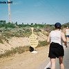 "Laura reaches the 20-mile mark (where the vultures start circling).  The signs make reference to the legend of the Greek runner Pheidippides, who ran 26 miles to announce to the Athenians that they had prevailed in battle.  Legend says he reached the city, said ""Rejoice, we conquer"" and fell over dead."