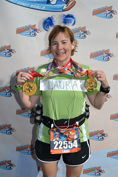 Laura poses with her Mickey Mouse marathon medal and her Goofy's Challenge medal.