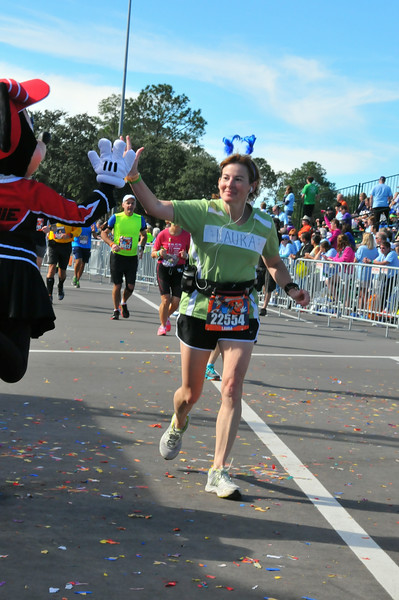 Minnie Mouse gives Laura a high-five at the finish line!