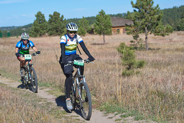 Sophomore girls Amee Steinwand, Cheyenne Mtn, and Anna Suter, Team Evergreen, are enjoying a recovery ride through a meadow after a climb. Photo Carrie Dittmer.
