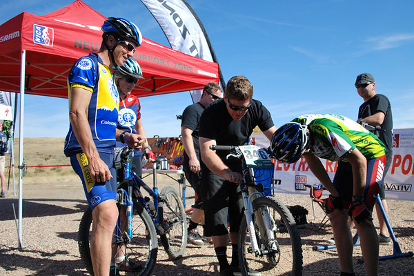 Mike and Heidi Kloser watch as Christian receives some mechanical support from John Dawson at the SRAM tent.