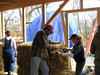 Some other workers beveling a strawbale beside a window.  Beveling the strawbales allows more light in through the windows.