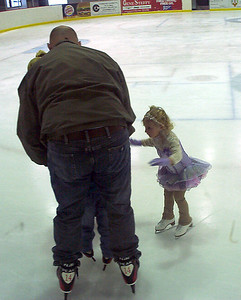 Nolan's dad and Rachel try to help Nolan steady himself on the ice.