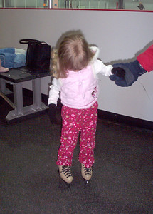 Friend Taylor checks out her skates -- she was very excited to try skating for the first time.